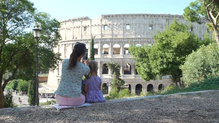 gladiador : Young Mother with her Cute Little Daughter Taking Photos of Colosseum (Coliseum) with Smartphone in Sunny Day. Concept of Holidays, Vacations and Travel in Europe