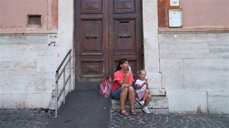 glaces italiennes : Beautiful Woman with her Cute Little Daughter Sitting on the Steps of Building and Eating Italian Ice Cream (Gelato) in Rome. Family Holidays, Vacation and People Concept Vidéos Libres De Droits