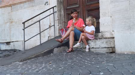 vacations cones : Young Woman with her Daughter Eating Traditional Italian Ice Cream called Gelato in the Waffle Cone on a Street of Rome, Italy. Holidays, Travel and Street Food Concept