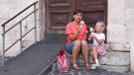 vacations cones : Young Woman with her Daughter Enjoying Tasty Cone with an Italian Homemade Gelato on a Street of Rome, Italy. Holidays, Travel and Street Food Concept Stock Footage