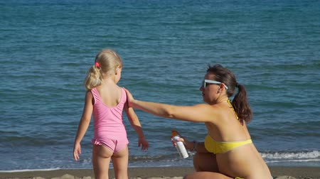 sunblock : Young Woman Applying Sunscreen on her Little Daughter at the Beach. Summer Vacation with Children. Family Holiday on Resort. Slow Motion. Healthcare and Sun Protection at Travel Time Concept Stock Footage