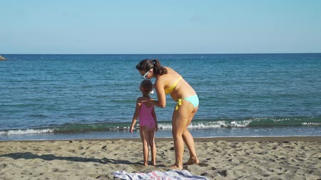 uv : Young Mother Applying Sunblock Cream on her Little Daughter at the Beach in Slow Motion. Children Healthcare and Sun Protection at Travel Time. Family Holiday on Resort