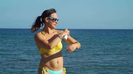 koruma : Smiling Woman Applying Sunblock Cream on the Beach in Slow Motion. Female Using Sunscreen to Protect from Sun during Summer Sea Vacation. Healthcare and Sun Protection at Travel Time Concept