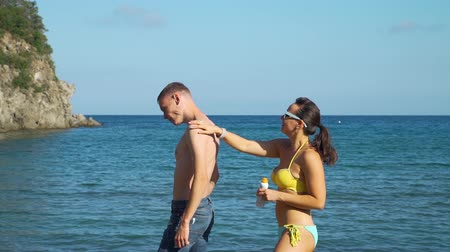 ultraviolet : Young Woman Applying Sunscreen to her Husband. Family Using Sunblock Cream to Protect from Sun during Summer Sea Vacation. Healthcare and Sun Protection at Travel Time Concept