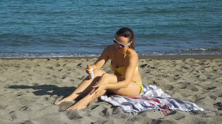 koruma : Young Woman Applying Suntan Lotion on the Beach in Sunny Summer Day. Holidays, Vacation and Travel Concept