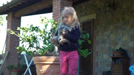 toszkána : Little Girl Holding Cute Gray and Ginger Kittens in her Hands near the Italian House. Happy Childhood, Pets and Animals Concept