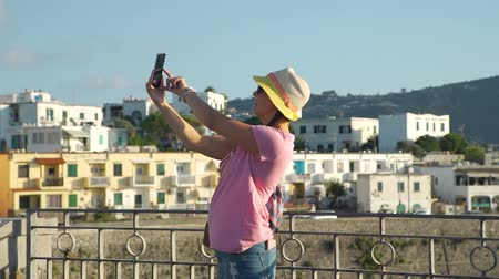 tomando : Young Woman in a Hat Taking Selfie with Smartphone in a Street of Italian City. Concept of Holidays, Vacations and Travel in Europe