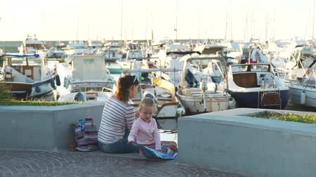 lancha : Cute Little Girl Reading Tourist Map while her Mother Using Mobile Phone. They Sitting on the Steps of the Port of Forio Town on Ischia Island. Lots of Yachts and Boats are on the Background. Vídeos