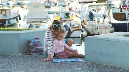 lancha : Young Woman with her Cute Little Daughter Reading Tourist Map in Port of Forio Town at Sunset. Lots of Boats and Yachts are on the Background. Concept of Holidays, Vacations and Travel in Europe