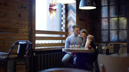 встреча : Beautiful Young Couple in Love Dating in a Coffee Shop. Two cups of Coffee and Red Rose Flower on the Table. Slow Motion. Love, Romance, Dating, Celebrating Valentine Day Concept