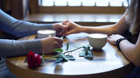 встреча : Close Up of Couple Dating in a Coffee Shop. They Holding by Hands and Enjoying Time Together. Slow Motion. Love, Romance, Dating, Celebrating Valentine Day Concept