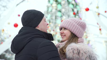 ice skating : Happy Loving Couple Standing near Street Christmas Decorations. Man Straightens Winter Hat to his Girlfriend. Slow Motion. Lifestyle, Love, Dating and Romantic Relationships Concept Stock Footage