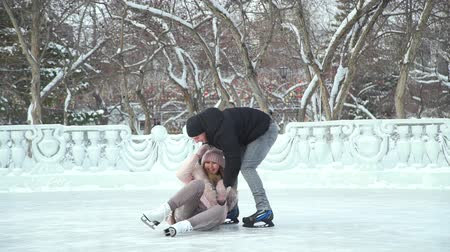 outdoor hobby : Man Helping Young Woman to Rise Up on Open Ice Skating Rink. Slow Motion. People, Winter, Friendship, Sport and Leisure Concept