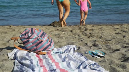 тапочка : Close Up of Mother and her Daughter Going into Water to Swim. They Enjoying Time Together on the Beach in Summer Day. Backpack, Beach Towel and Rubber Slippers are on the Foreground. Selective Focus.