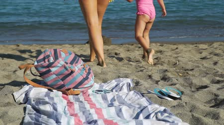тапочка : Close Up of Mother and Little Daughter Going into Water to Swim. They Enjoying Time Together on the Beach in Summer Day. Backpack, Beach Towel and Rubber Slippers are on the Foreground.