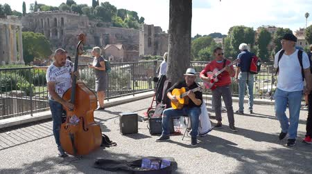 akusztikus : Rome, Italy - October 5, 2019: Performance of Street Musicians with Acoustic Instruments over Ancient Ruins of the Forum in Rome. Concept of Holidays, Vacations and Travel in Europe