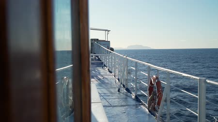lifebuoy : The Deck of a Tyrrhenian Ferry Heading Across a Sea with the Land in the Distance. Slow Motion. Concept of Holidays, Vacations and Travel Stock Footage