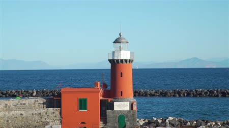 napoli : Red Lighthouse Tower on Stone Breakwater near Ischia Porto in Sunny Day. View from the Ferry. Concept of Holidays, Vacations and Travel in Europe