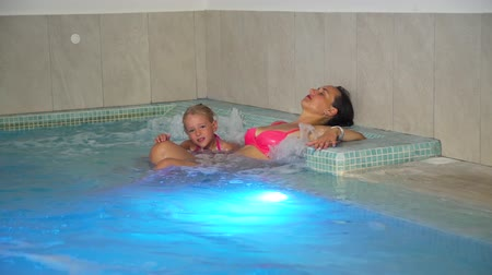 zen como : Young Woman and her Little Daughter Enjoying Hydro Massage in a Pool. Family Spa Hydrotherapy. Relax and Spa Concept