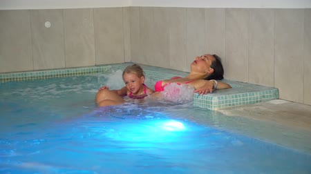 zen como : Young Woman and her Little Daughter Enjoying Hydro Massage in a Pool. Family Spa Hydrotherapy. Slow Motion. Relax and Spa Concept