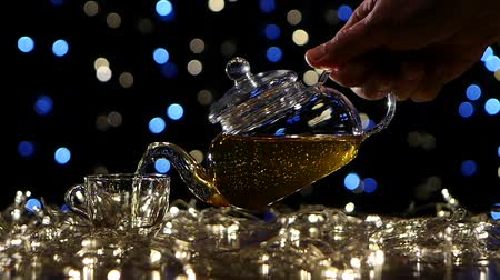 evaporate : Tea from the teapot is poured into small glass cup, slow motion Stock Footage