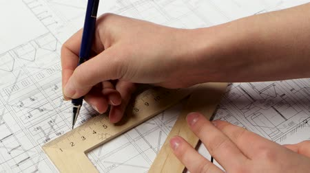 chancellery : Girl using the ruler draws new lines for building the building. Close up Stock Footage