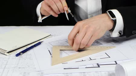 chancellery : Businessman with a compass and ruler makes measurements for the drawing. Close up Stock Footage