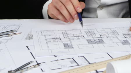 chancellery : Designer sits at the table, chooses a drawing that is more optimal for him. Close up Stock Footage
