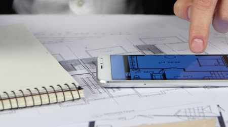 chancellery : Engineer looks at the drawings and graphics in the phone. Close up Stock Footage