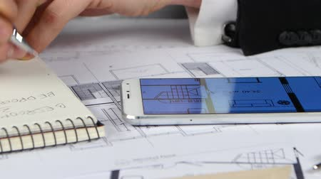 chancellery : Businessman looks at blueprints and graphics in the phone. Close up Stock Footage