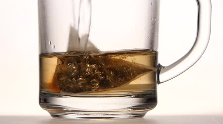 tea bag : Pyramid tea bag in cup is poured over boiling water Stock Footage