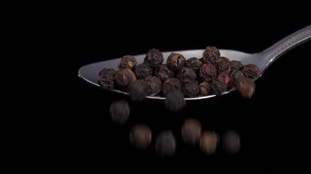 concoction : Black pepper peas falling from the iron spoon, black background, slow motion Stock Footage