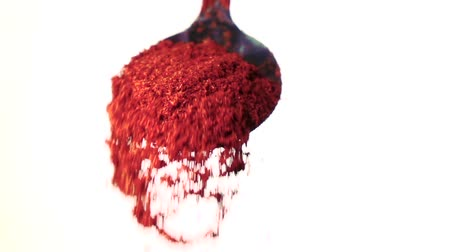 spices : Red chili powder falling from the iron spoon. White background. Slow motion