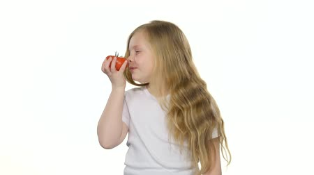 admires : Child looks at a tomato, admires it and smiles. White background