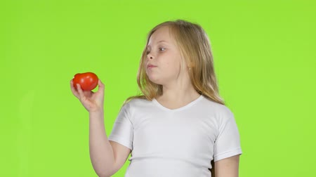 admires : Little girl looks at a tomato, admires it and shows a thumbs up. Green screen