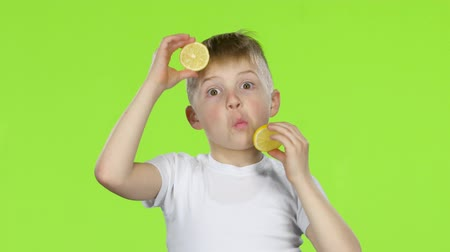 kiddy : Children with slices of lemon licks them and shows grimaces. Green screen Stock Footage