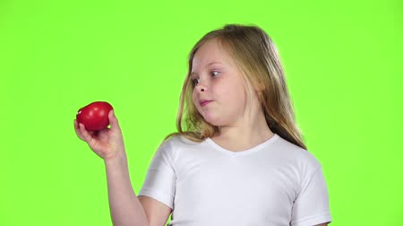 admires : Little girl looks at a tomato, admires it and shows a thumbs up. Green screen. Slow motion