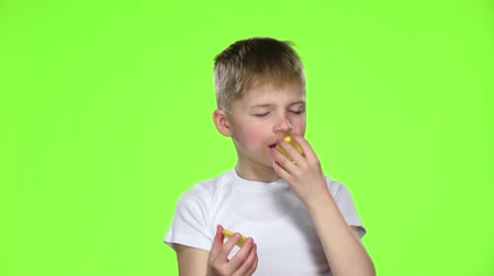 kiddy : Small boy holds a slice of a lemon licks and curls from acid. Green screen. Slow motion
