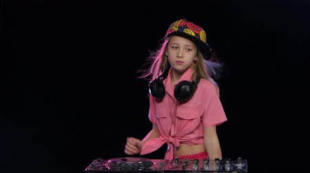płyta winylowa : Teenage girl plays music and dances at dj table. Studio Wideo