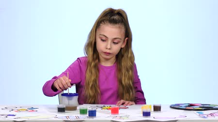 admires : Children paint a picture with pencils and admire their work. Close up. White background. Time lapse Stock Footage