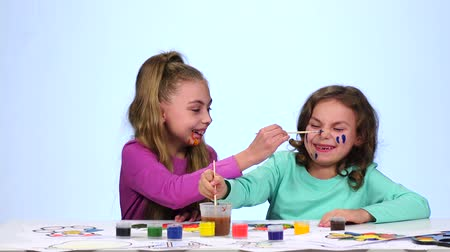 admires : Two little sisters decorate their faces with colorful colors. Close up. White background Stock Footage