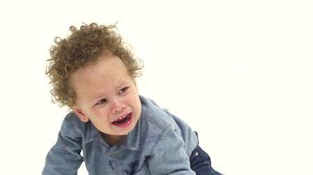 haywire : Child sits on the floor and cries, he is in sorrow. White background. Slow motion Stock Footage