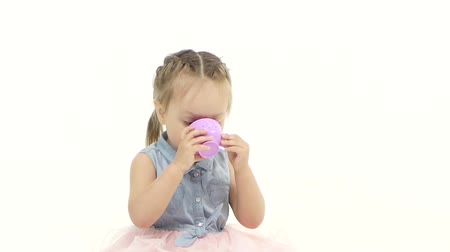 kiddy : Child sits on a pillow and drinks tea. White background. Slow motion Stock Footage
