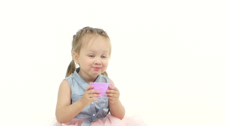 kiddy : Baby sits on the floor and drinks tea. White background. Slow motion