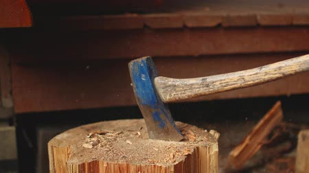 раскол : A slow-motion video of an axe splitting a piece of wood on a stump.