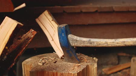 fülke : A slow-motion video of an axe splitting a piece of wood on a stump.