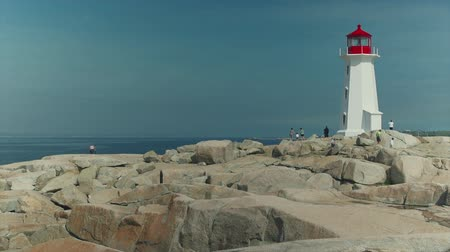 światło : Tourists climb the rocky shore around Nova Scotias famous Peggys Cove Lighhouse.