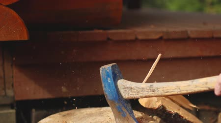machado : A slow-motion video of an axe splitting a piece of wood on a stump.