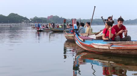 u boats : MANDALAY, MYANMAR- DECEMBER 08 , 2015: Boatmen taking tourists on sunset sightseeing trip in lake Amarapura, famous tourist attraction in Mandalay. Stock Footage