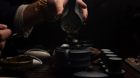 Pouring tea into a clay teapot is another way Stock Footage